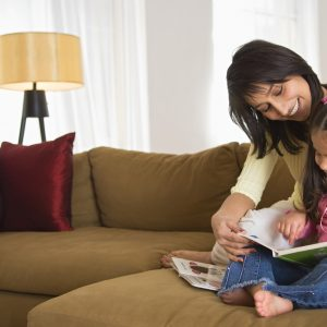 mother and young daughter reading together on the couch