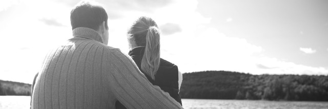 Couple sitting on dock in lake