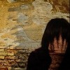woman crying near a brick wall