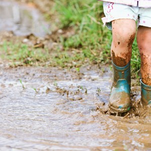 Child's feet stomping in a mud puddle.