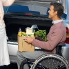 Man in a wheelchair holding groceries.