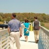 Three people, two men one woman in a bright blue dress, walking on a footbridge. They are facing away from the camera.