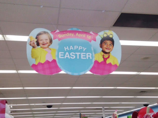 Easter display ad hanging from Walgreen's ceiling, has two children in eggs. A young girl with Down syndrome and a young boy.