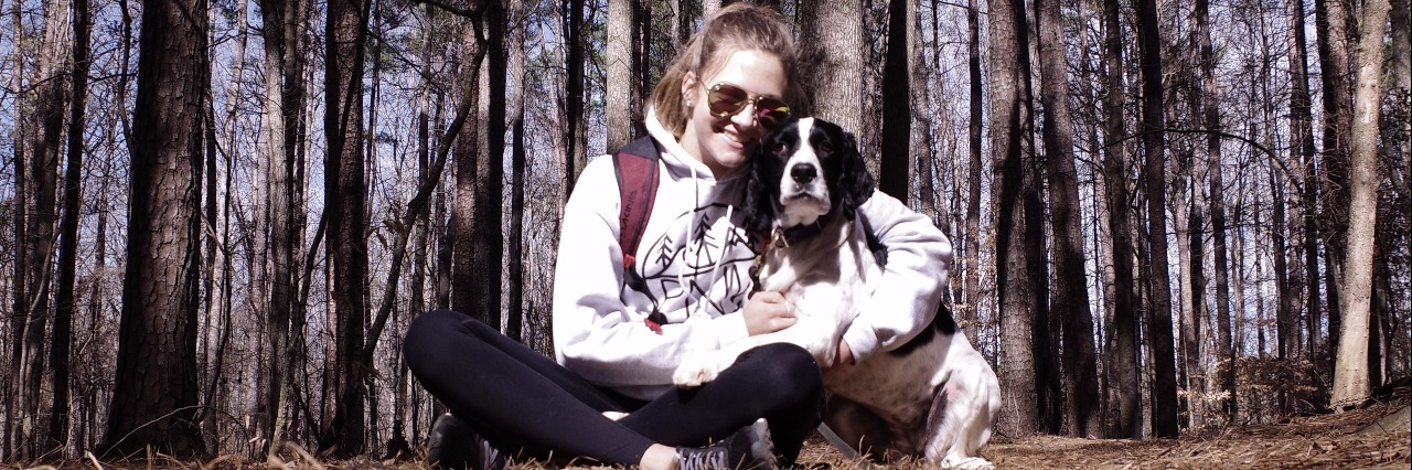 girl sitting in woods with dog