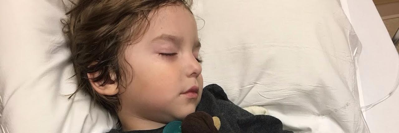 little boy asleep in the hospital