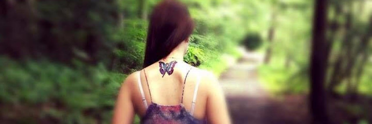 woman with a butterfly tattoo walking barefoot on a path through the woods