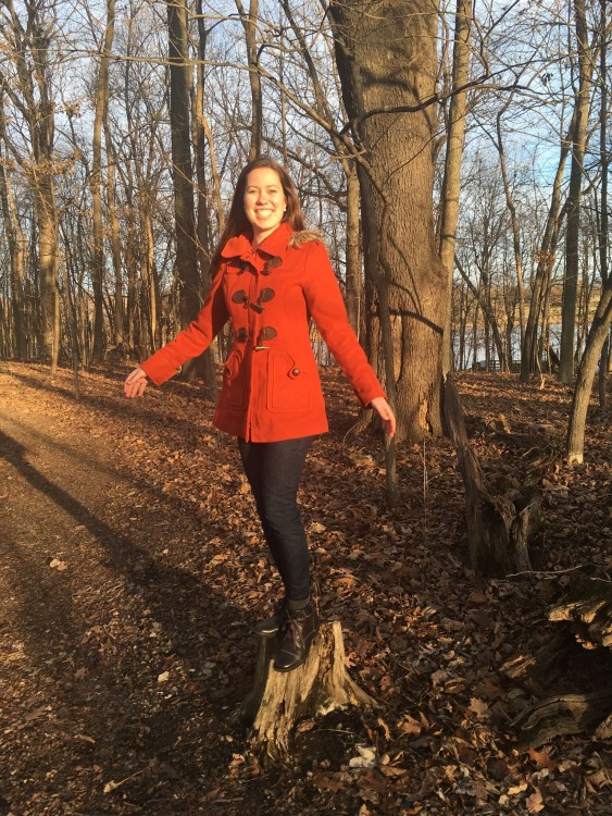 woman in red coat standing on a tree stump in the woods