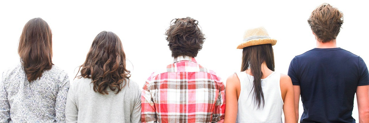 Rear view of friends standing on stone wall