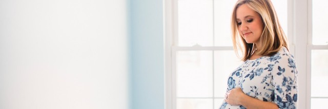 pregnant woman standing by window