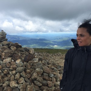 woman standing at top of mountain in front of pile of rocks