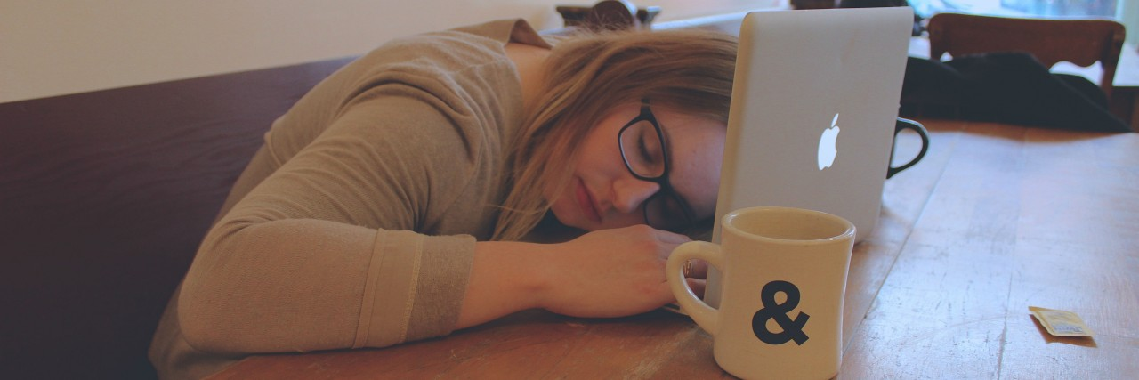 A woman sits at a table, her head resting on her laptop, coffee mug nearby.