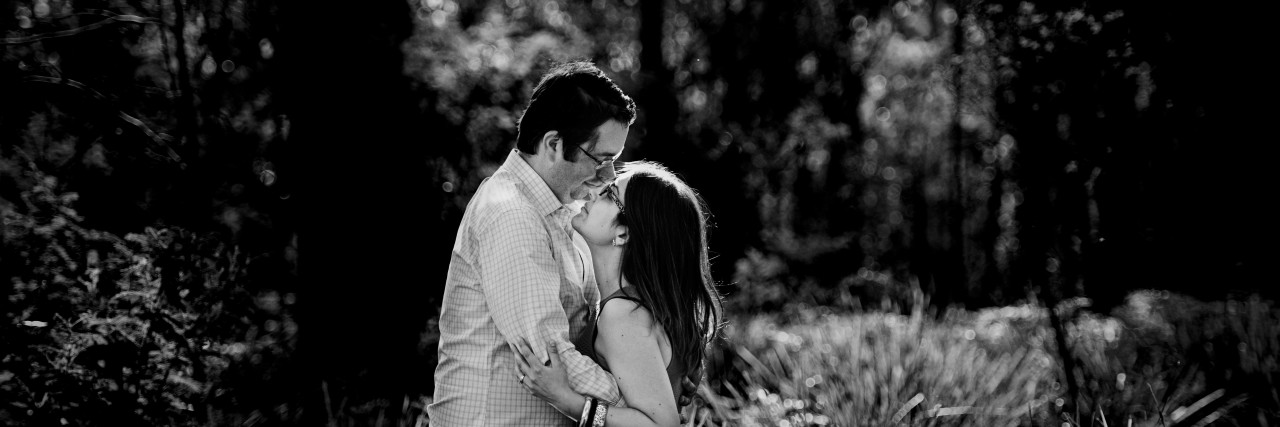 husband and wife kissing in forest