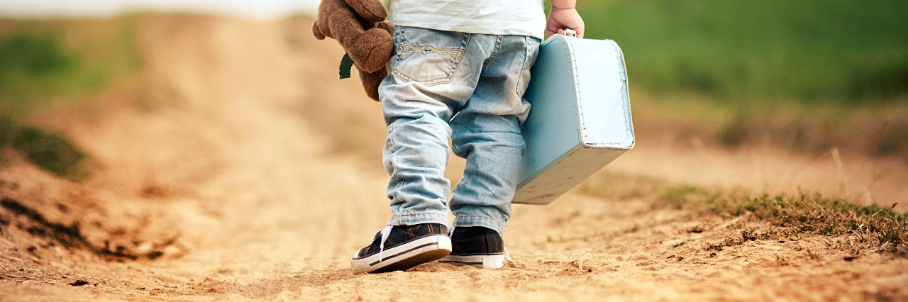Back of little boy walking on a path, he is wearing a hat, and holding a teddy bear and a tiny suitcase