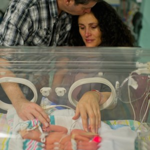 Parents with baby in incubator in hospital