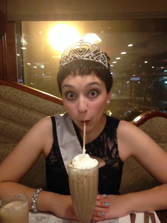young woman wearing a dress, tiara, and sash at a diner drinking a milkshake