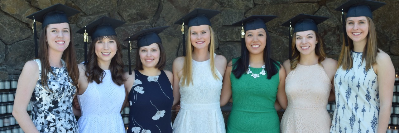 seven young women in dresses smile and wear graduation hats