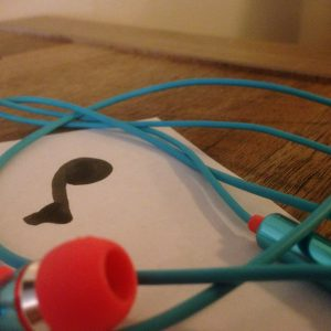 paper with music note on it and headphones nearby