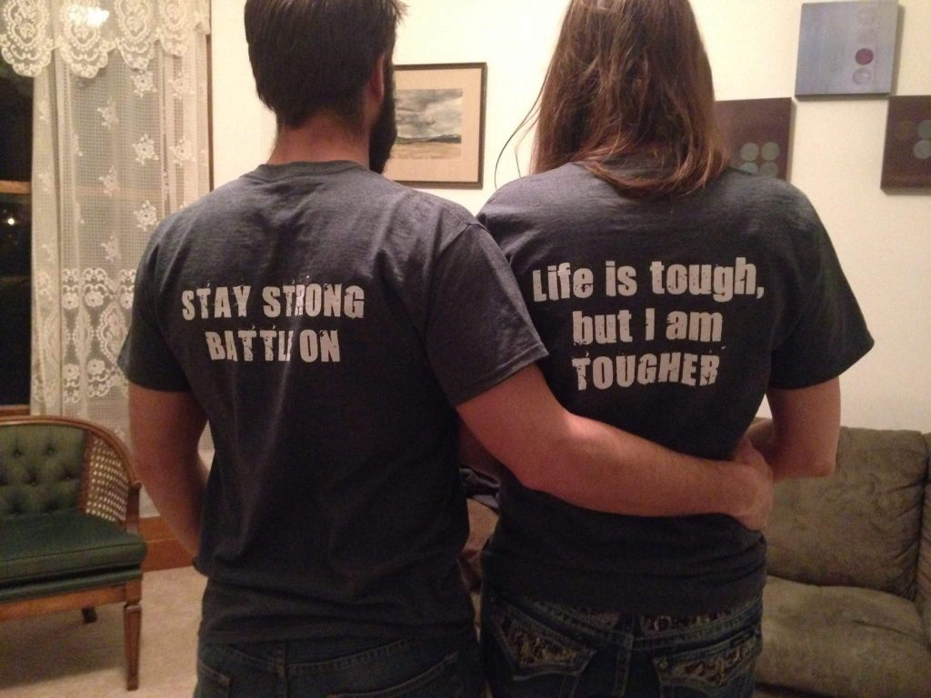 husband and wife wearing t-shirts that say 'stay strong, battle on' and 'life is tough, but I am tougher'