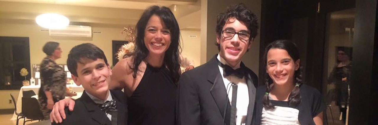 Kristin with her sons and daughter, dressed in formal attire at a party.
