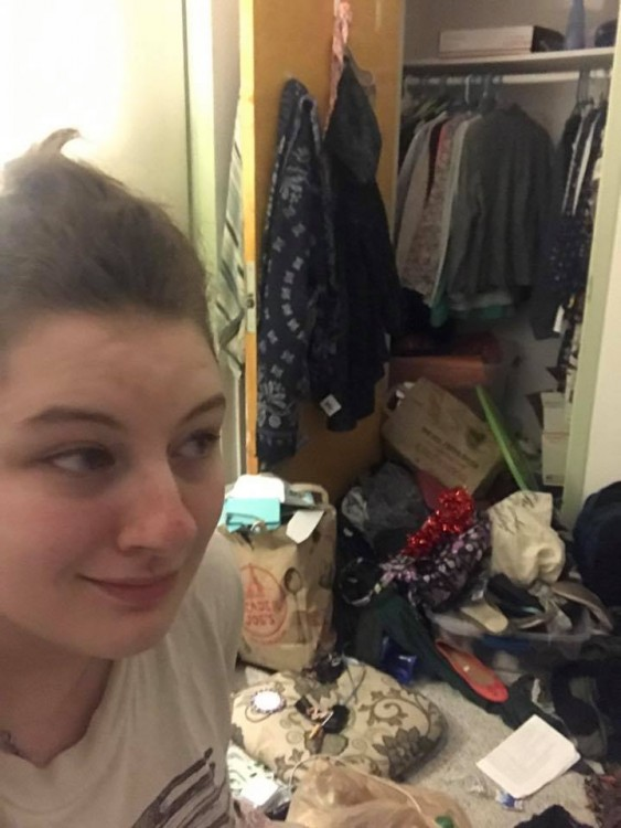 woman in dorm room with things on floor and coming out of closet