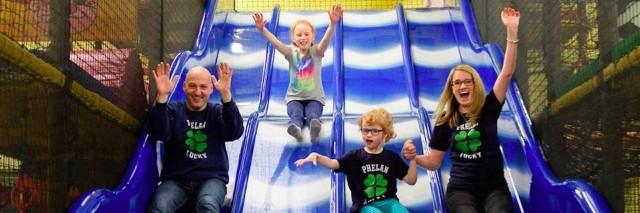 A family of four sliding down a blue slide