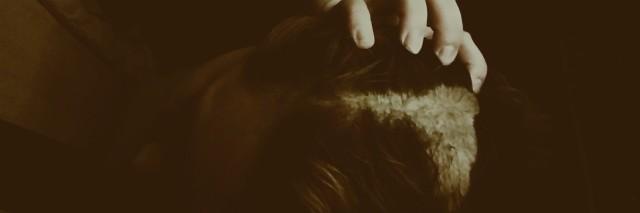 Woman with bald spot grabbing hair trichotillomania