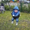 Baby with Down syndrome wearing a blue jacket and swinging outdoors