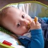 Baby with Down syndrome sitting in a bouncy chair wearing a blue jumper and gumming a piece of bread