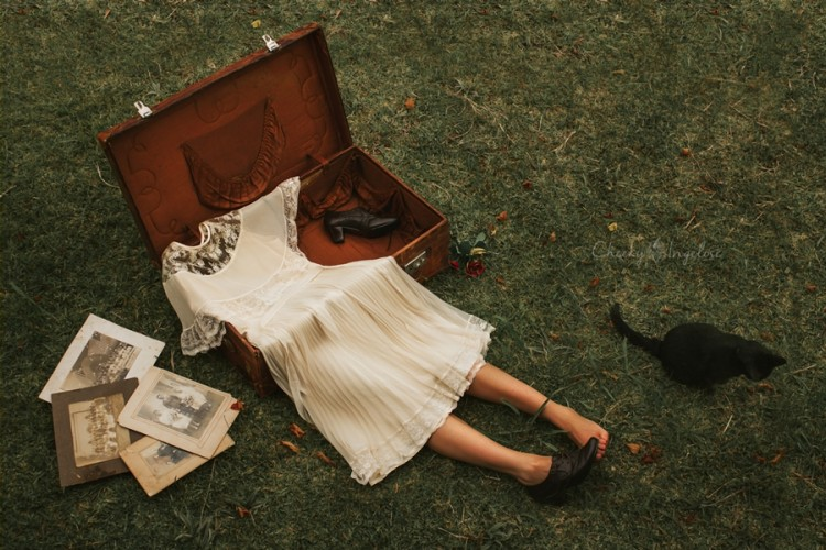 photo of a dress in a suitcase with legs sticking out
