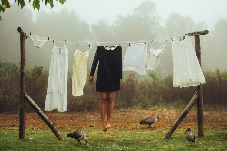 Woman without a head wearing a dress hanging on a clothes line.
