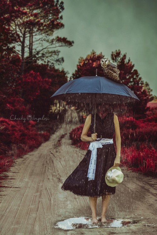 Woman without a head standing under an umbrella in the rain.