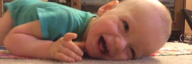 Happy baby laying on the floor on his tummy and smiling