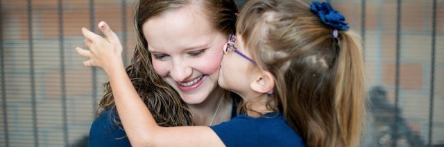 young daughter kissing her mother on the cheek