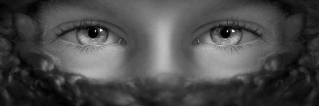 BLACK AND WHITE IMAGE OF EYES AND COVERED FACE
