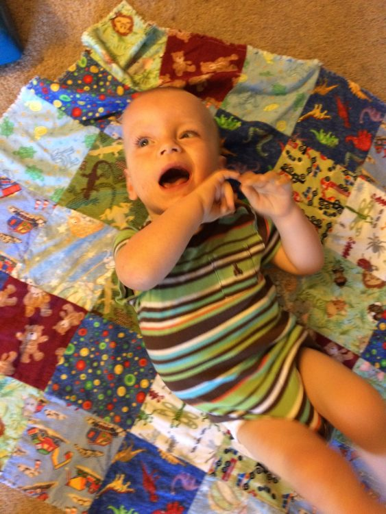 Baby laying on a quilt, smiling, and wearing a blue-green-brown stripped onsie