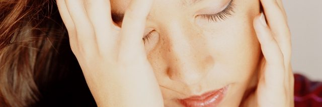 Close-up of woman holding her head