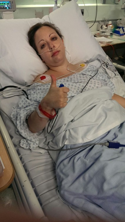 woman lying on hospital bed giving thumbs up
