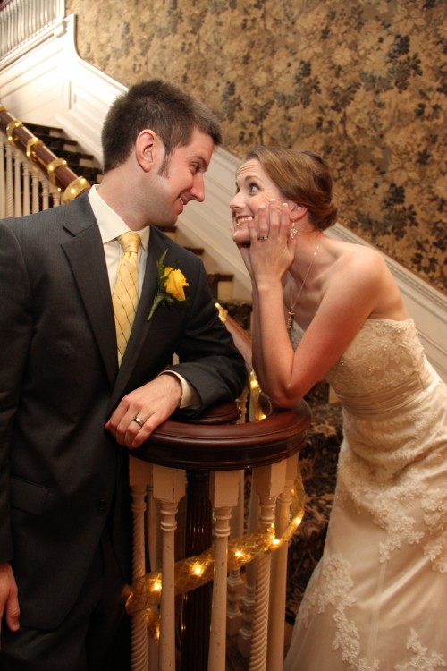 husband and wife leaning on a banister and smiling at each other
