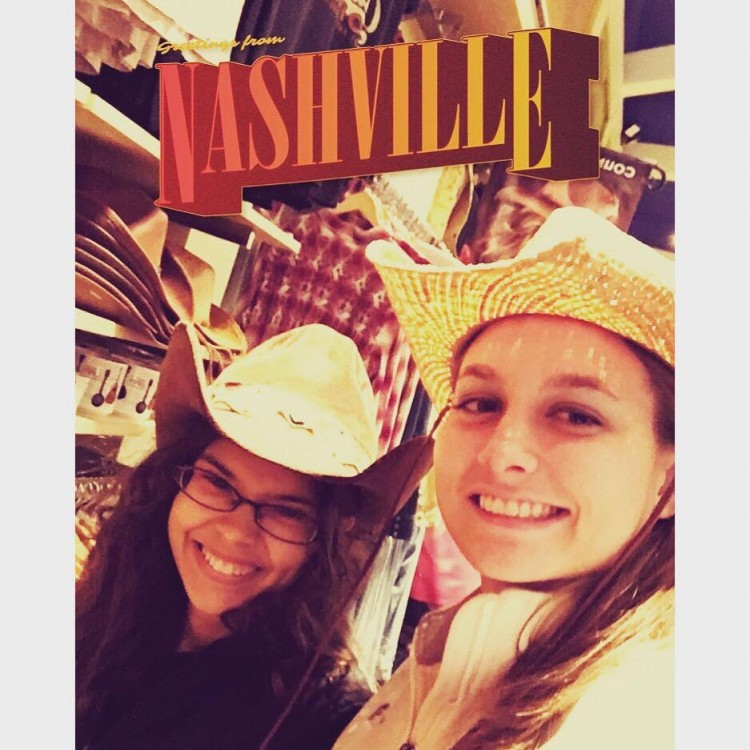 two women wearing cowboy hats in front of nashville background