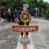 woman standing next to marker for zero degrees latitude in ecuador