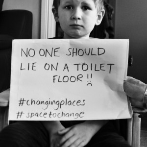 "Boy holding sign that reads ""No one should lie on a toilet floor."""