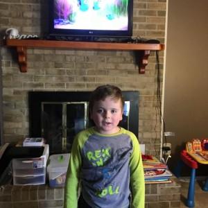Picture of Leo standing in front of the fireplace with the TV on the mantle, he is wearing a gray and green shirt.