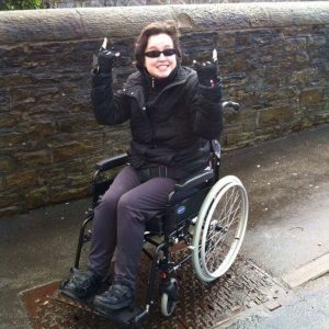 woman in a wheelchair giving a rock on hand sign