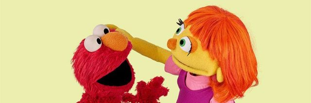 Julia and Elmos sitting down, Julia is patting Elmo's head