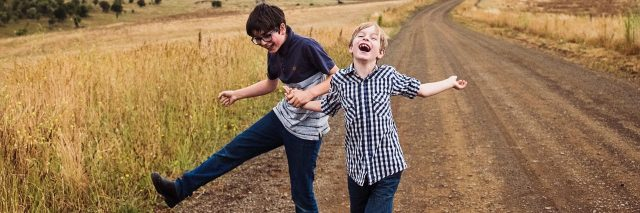 author's children laughing and smiling on road through fields