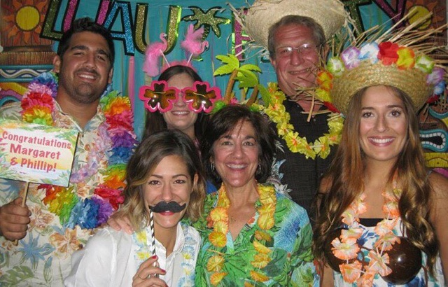 A group of 5 people in a photo booth wearing silly hats, over-sized glasses, in a Hawaiian themed background