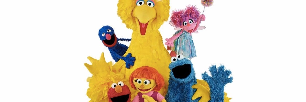 Photo of Sesame Street characters including Big Bird, Abby Kadabby, Grover, Elmo, Cookie Monster and Julia