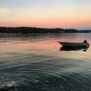 A rowboat sits in a middle of a lake with a beautiful sunset behind