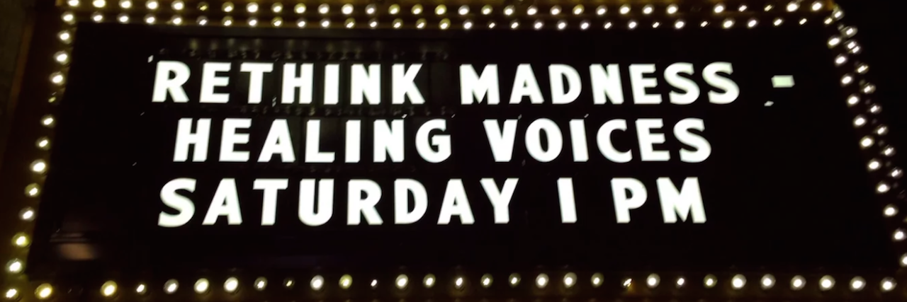 Sign on a movie theater that says: Rethink Madness, Healing Voices