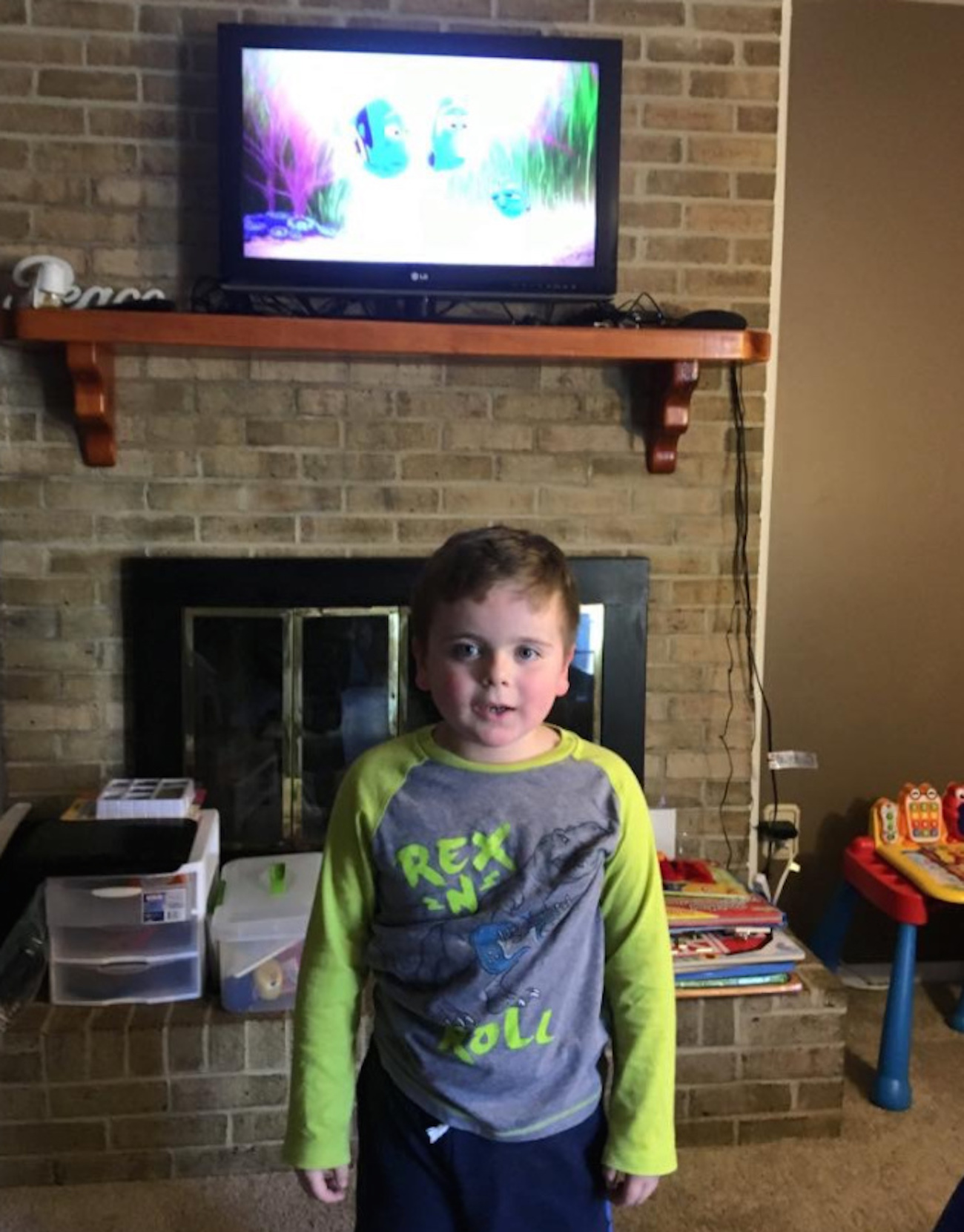 "Boy standing in living room in front of TV with the movie ""Finding Dory"" on"